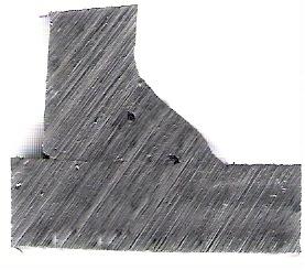 Macrografía de unión en ángulo de chapa gruesa (10mm), sin desbastar, con inclusiones de escoria