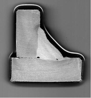 Macrografía de unión en ángulo de chapa gruesa (10mm), con falta de fusión entre pasadas y rechupe de raíz.